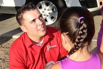 Marc Gonzales Owner of PremierX Pest speaking with little girl.